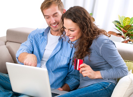 Happy Smiling Couple Using Credit Card to Shop Online